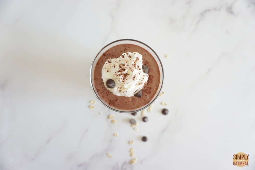 Vegan chocolate mousse oatmeal smoothie garnished with coconut cream, cocoa powder and vegan chocolate chips.