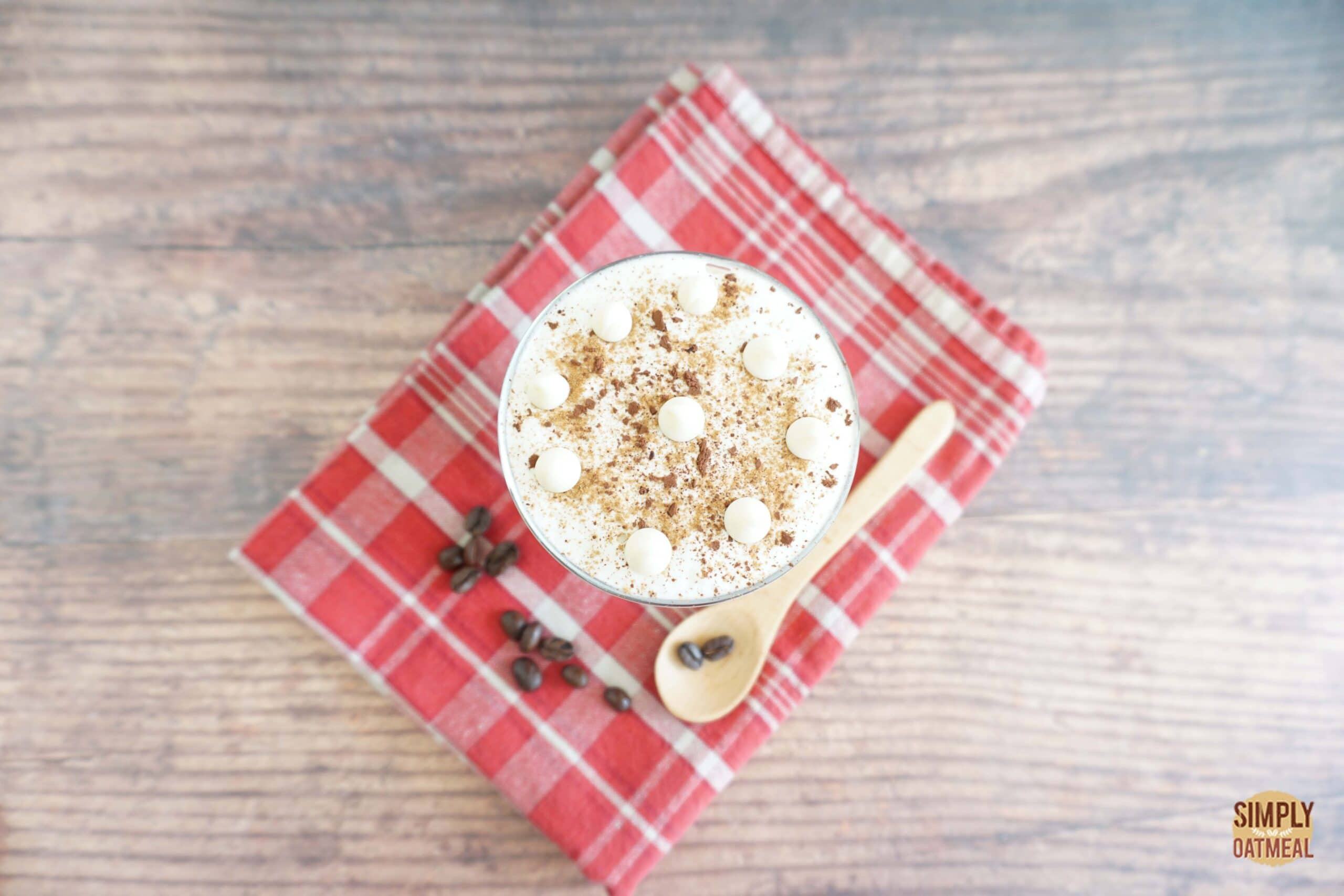 White chocolate mocha overnight oats topped with whipped cream, white chocolate chips and a sprinkle of cocoa powder.