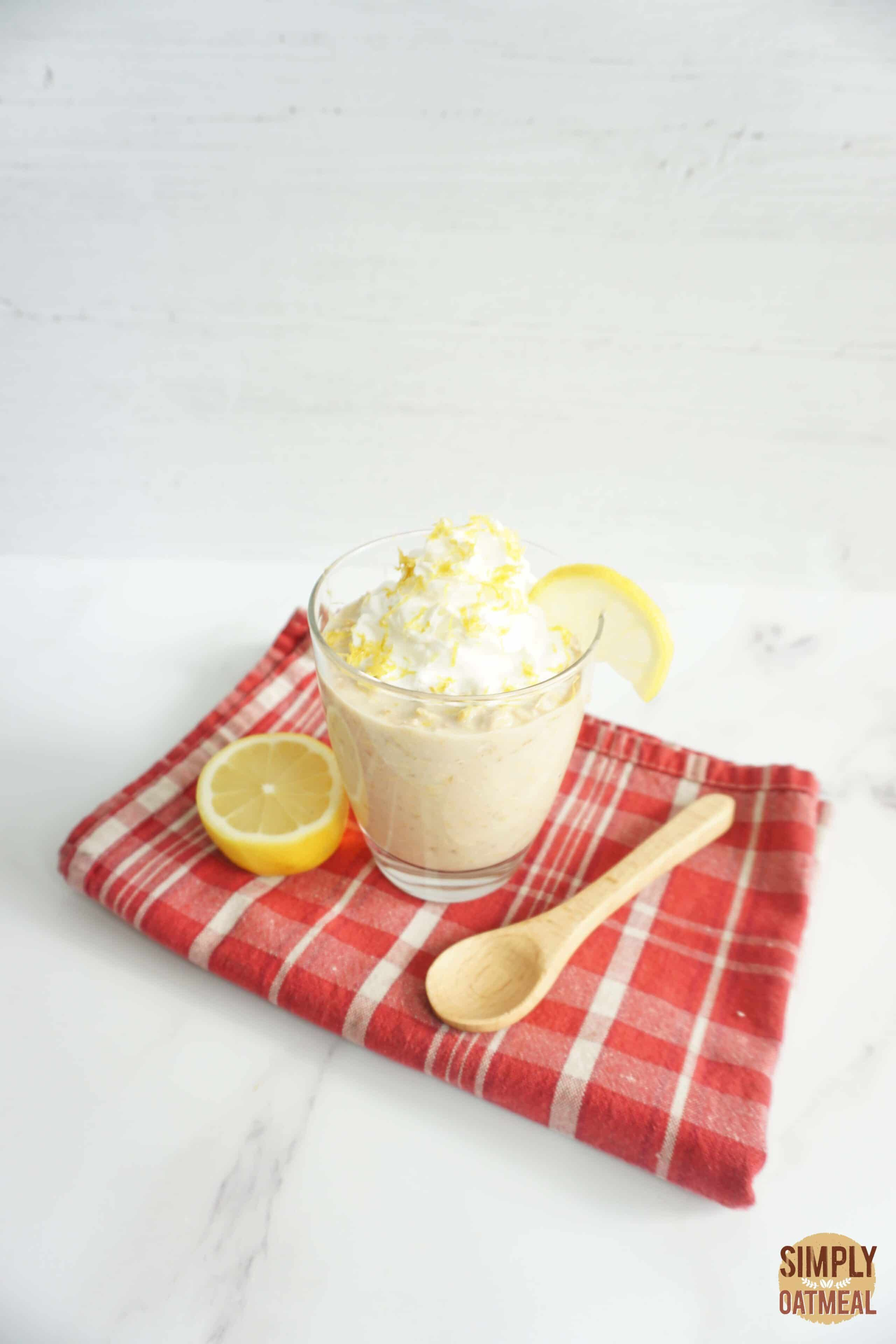 Serving of lemonade overnight oats in a glass cup topped with lemon zest and fresh lemon with a wooden spoon on the side