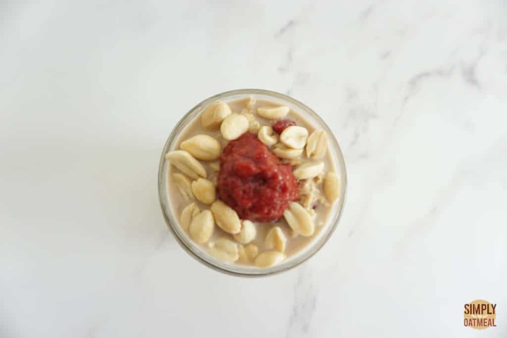 Serving of raspberry peanut butter overnight oats in a glass cup garnished with roasted peanuts and a scoop of raspberry chia jam.