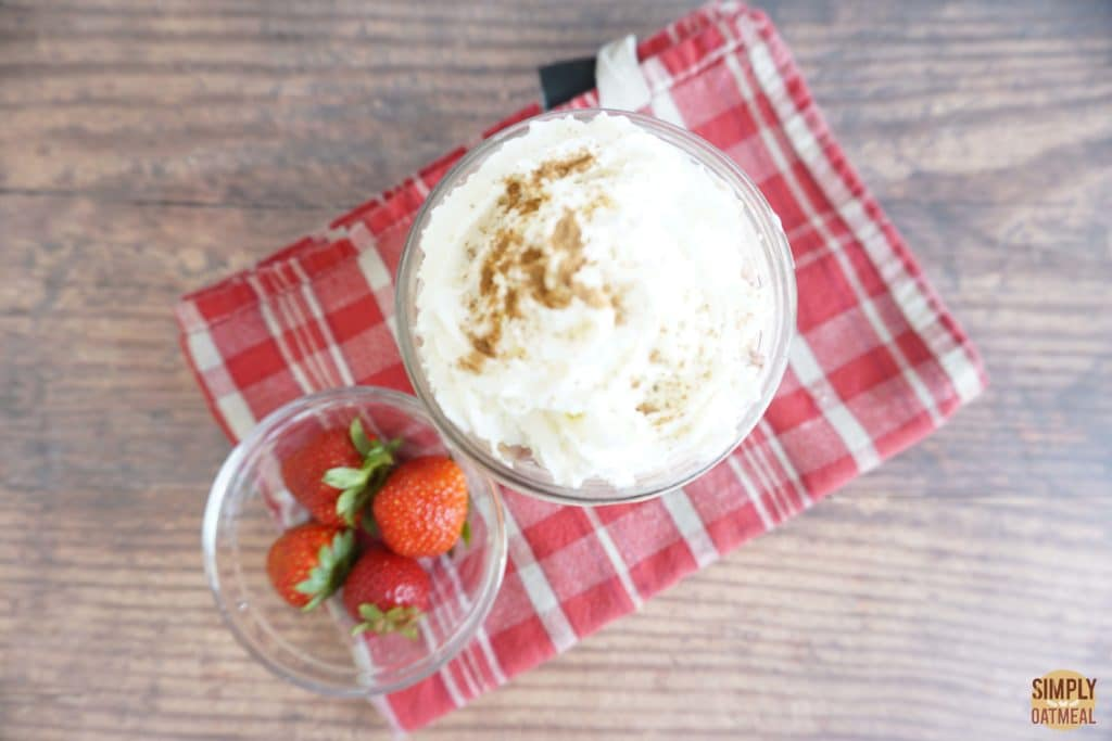 Serving of strawberry and cream overnight oats in a glass cup topped with fresh whipped cream sprinkled with cinnamon