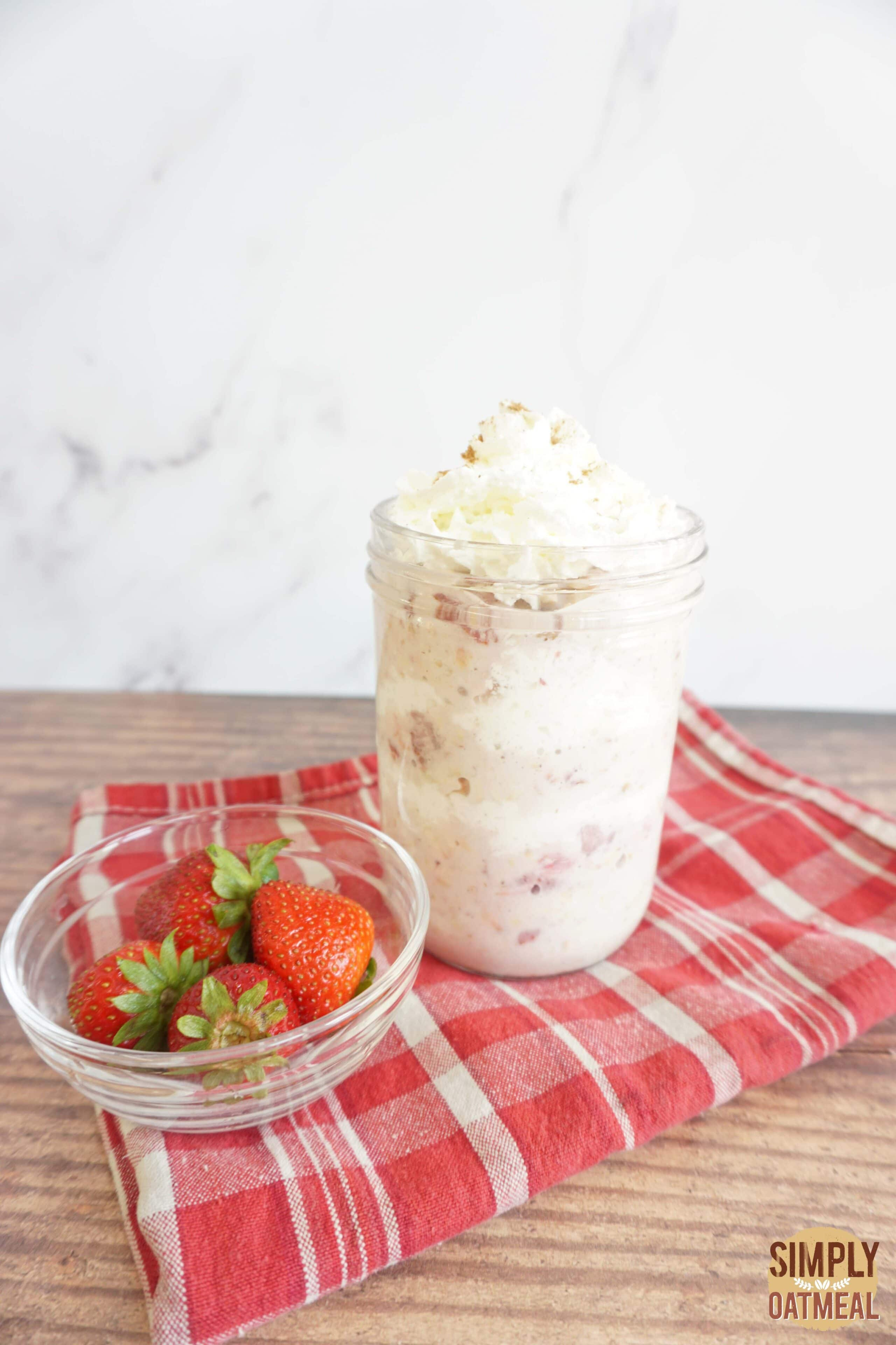 Strawberry and cream overnight oats in a mason jar with whipped cream and wild strawberries.