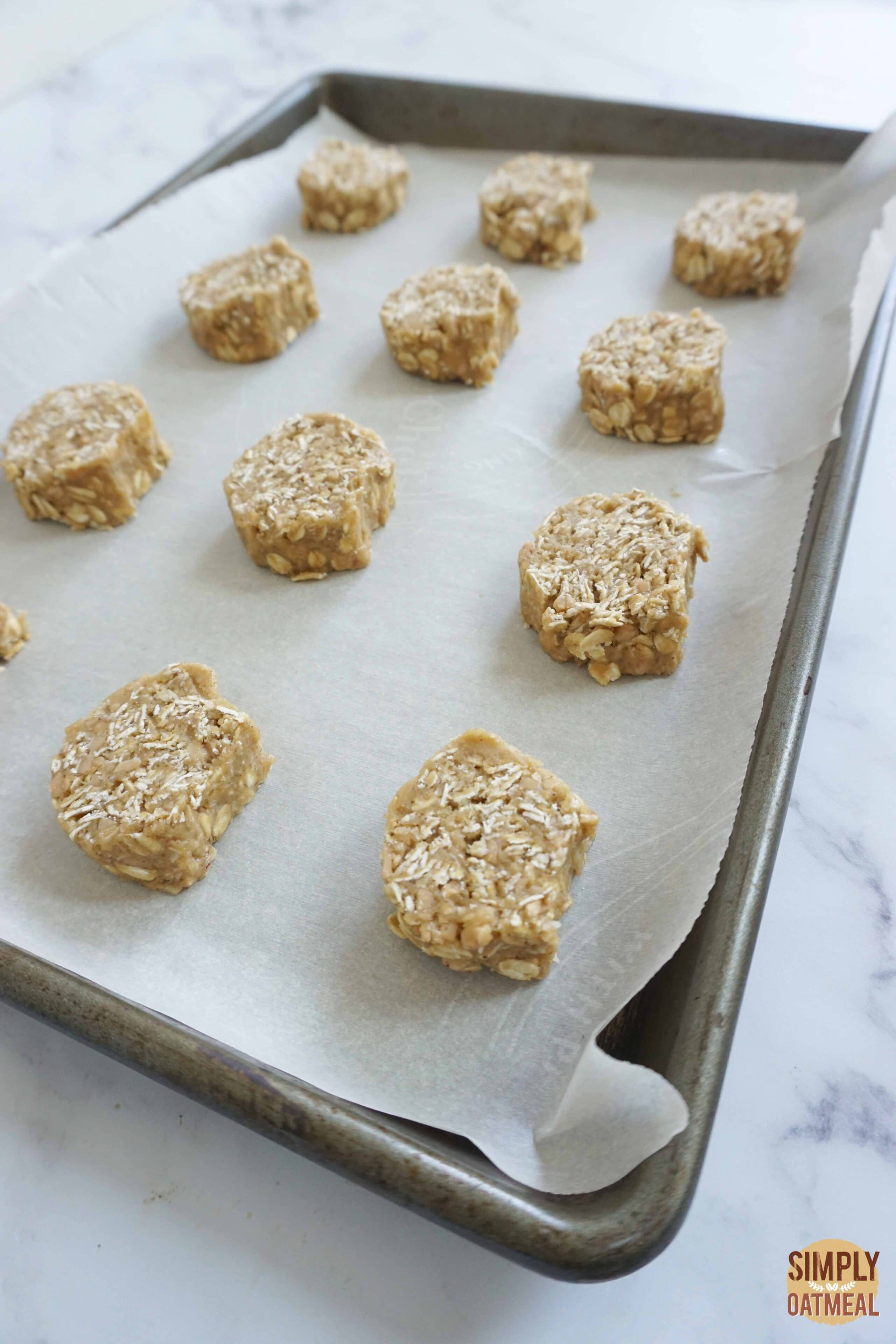 Raw toffee coconut oatmeal cookies on a parchment paper lined baking sheet