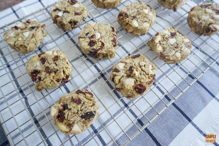 Hot white chocolate cherry oatmeal cookies cooling off on a wire rack