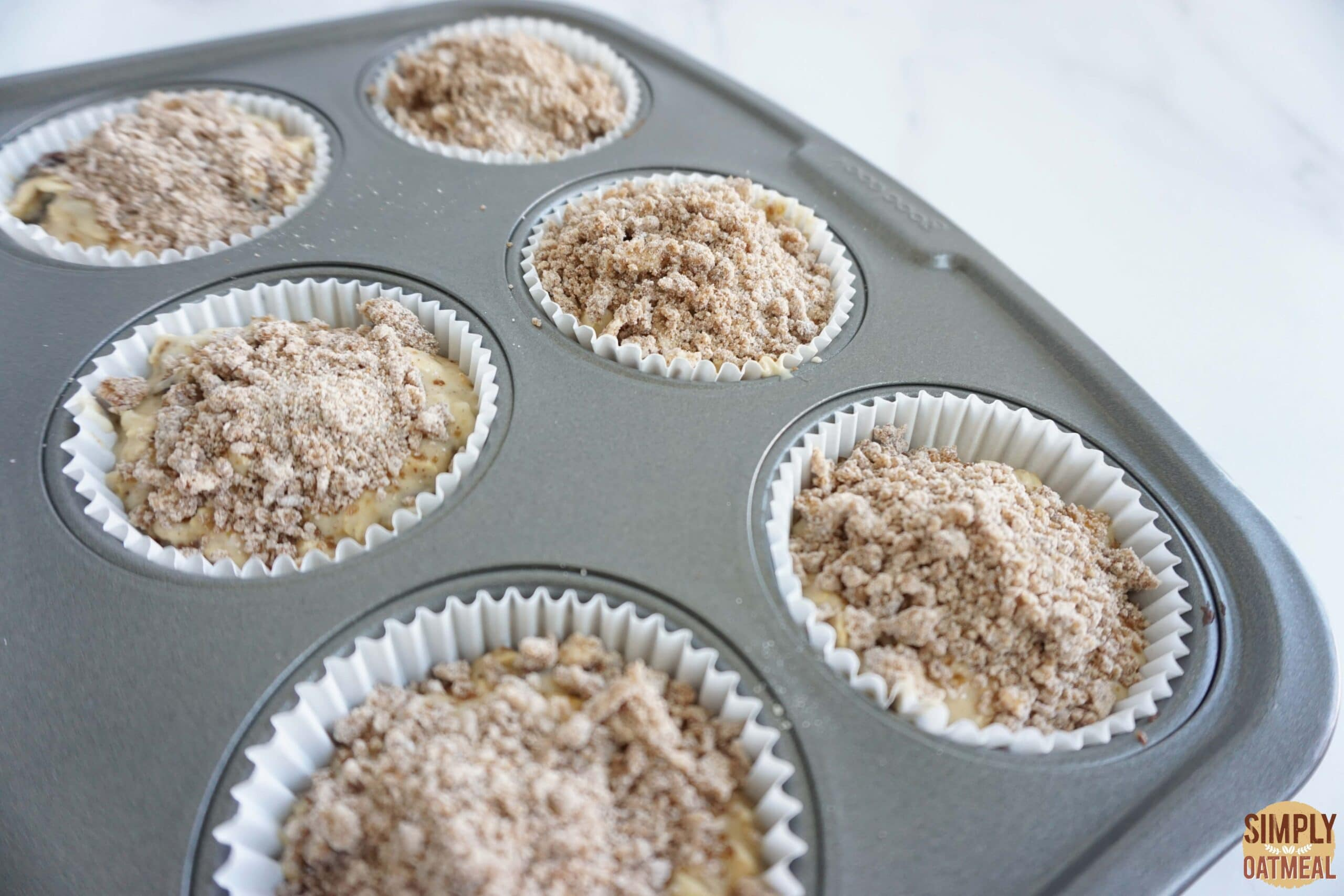 Baked cinnamon streusel oatmeal muffins in a muffin pan