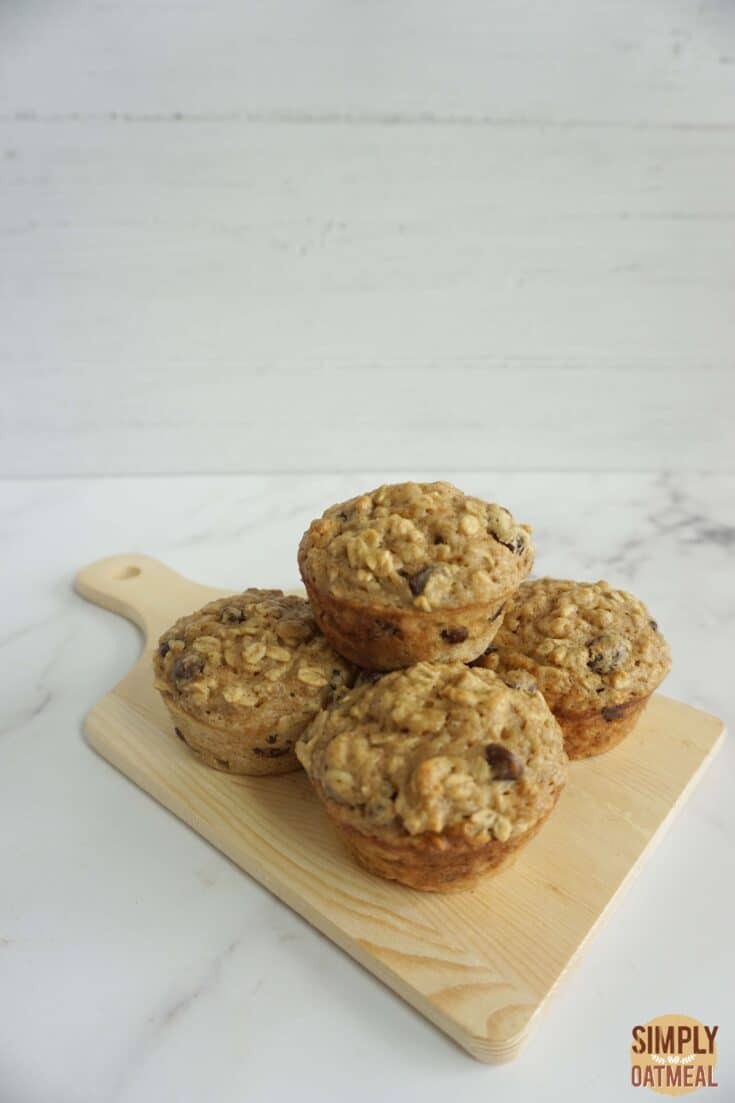 Fresh baked applesauce oatmeal muffins on a wooden plate