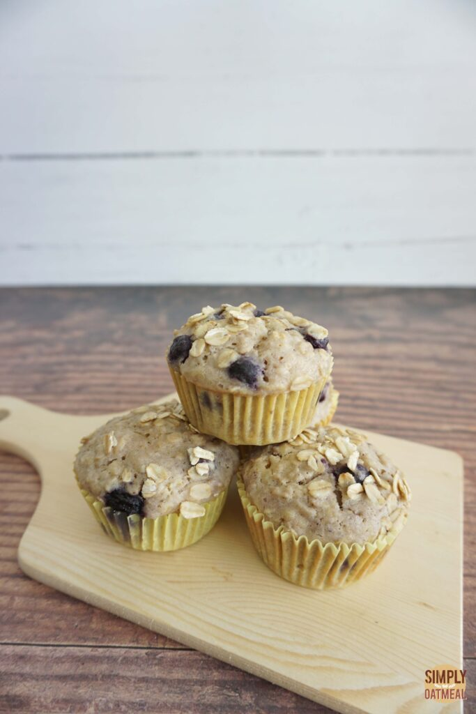 Fresh baked blueberry lemon oatmeal muffins on a wood plate