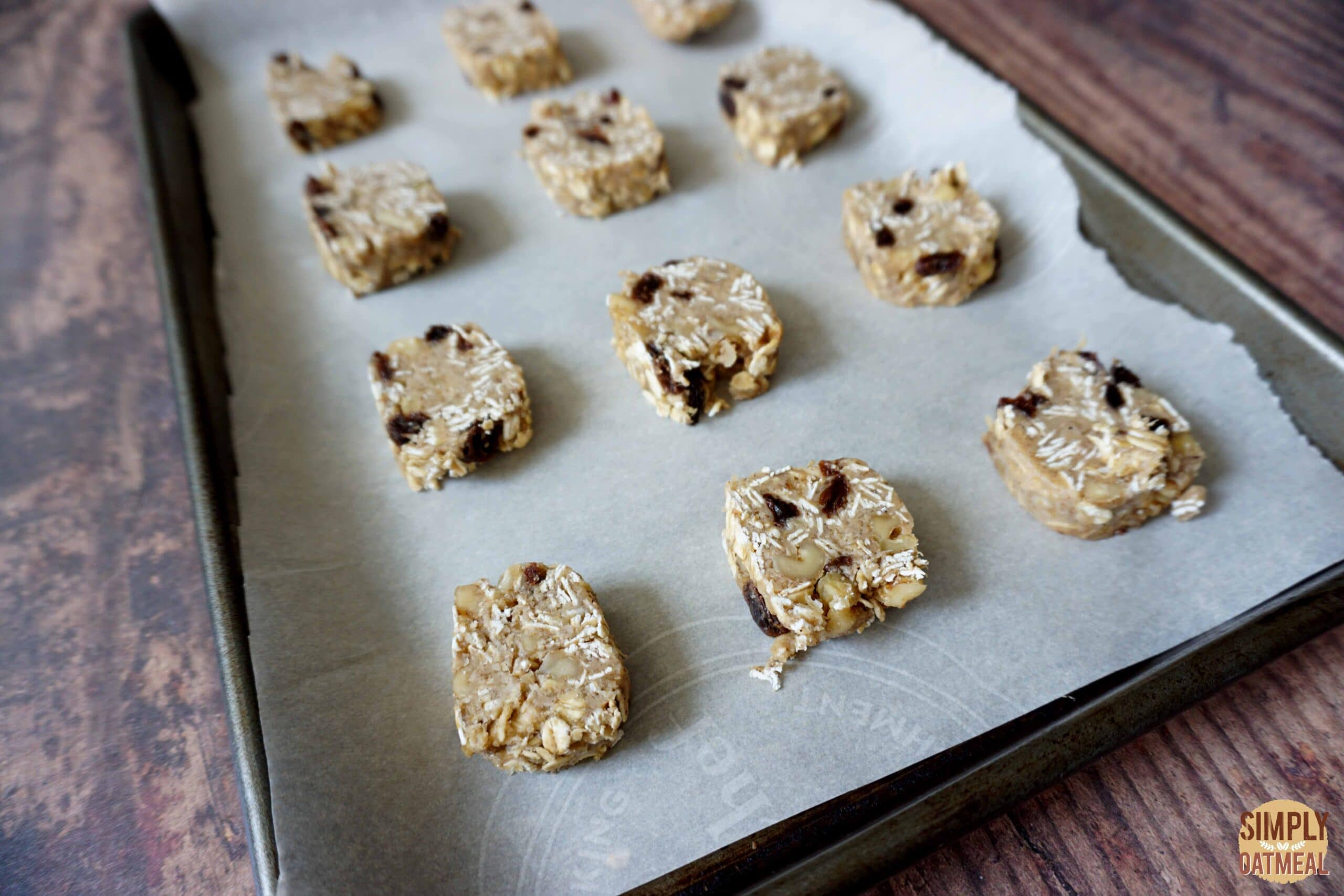 Raw oatmeal raisin cookies on a baking sheet lined with parchment paper