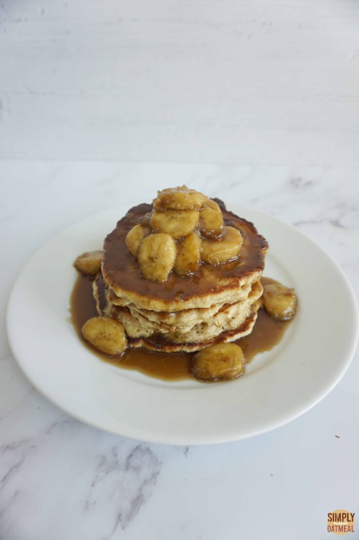 Banana butterscotch oatmeal pancakes stacked on a plate