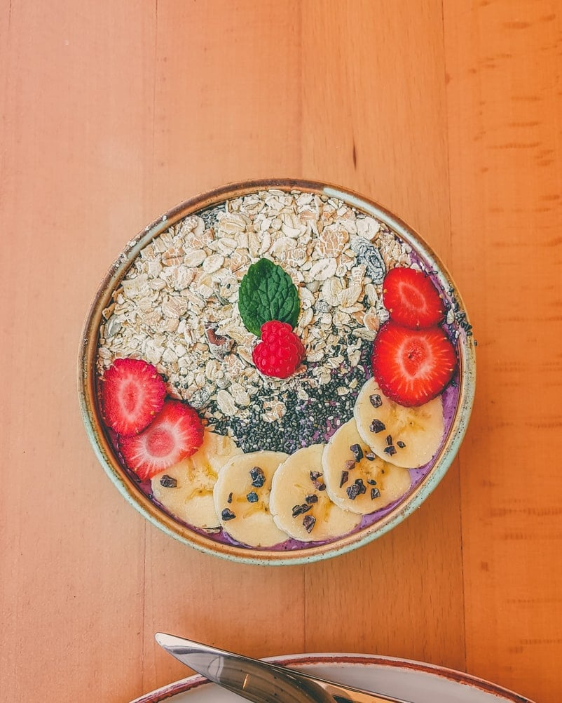 Bowl of oatmeal topped with superfood weight loss ingredients like banana, berries, chia seeds and cocoa nibs.