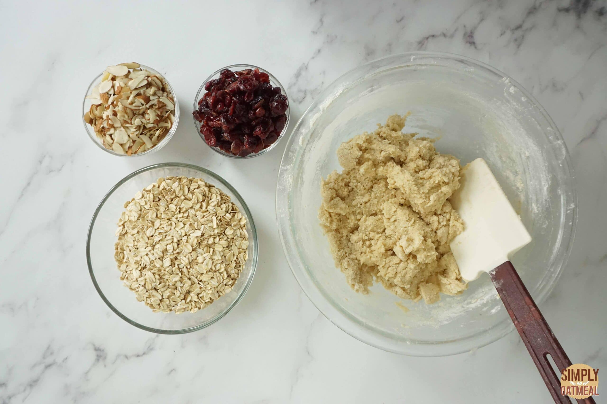 Fold dried cranberries and almonds into oatmeal cookie dough.