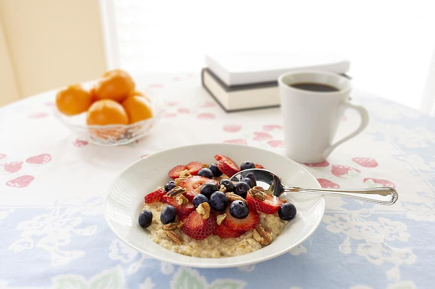 Steamy hot bowl of oatmeal topped with fresh berries and nuts. Hot coffee and fresh oranges on the side