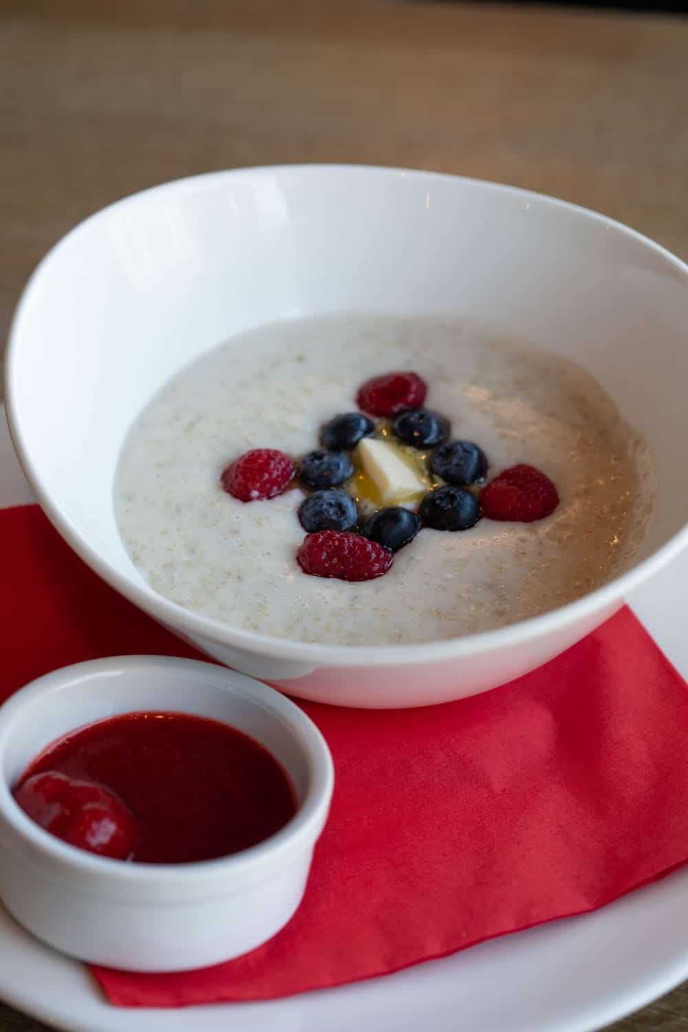 Cooked Irish oats is a white bowl with fresh berries on top
