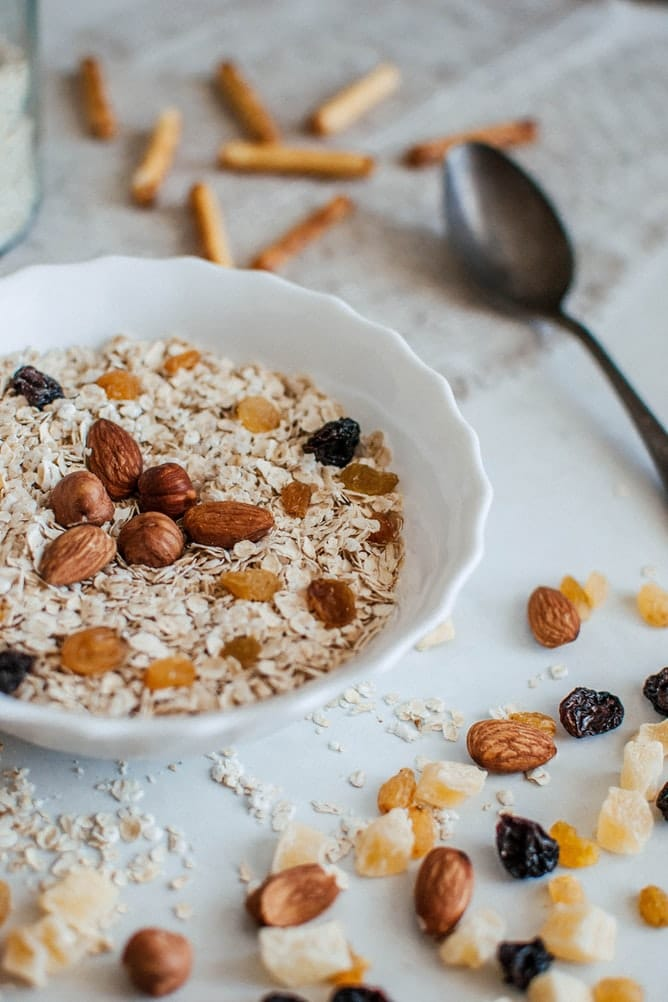 Bowl of oats topped with nuts and dried fruit.