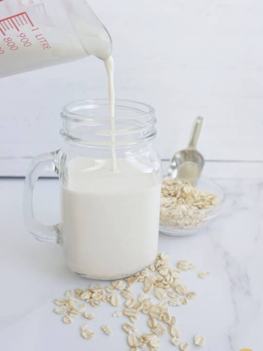 Pouring creamy oat milk without oil into a glass cup